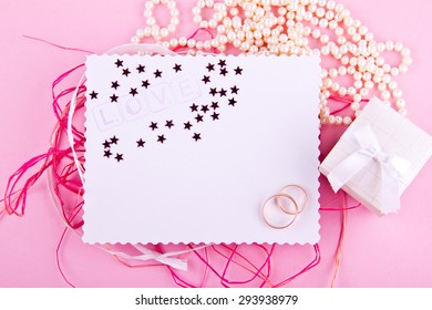 White greeting card with wavy edge is decorated with wedding rings and stars on pink background. Place for your text. Good for blogs, instagram, tweets.
