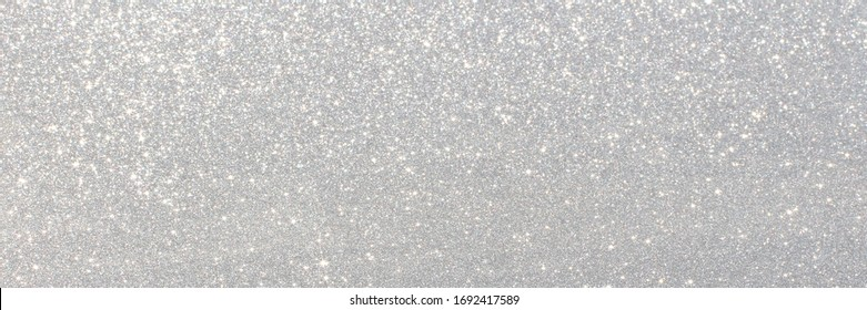 White and grey glitter bokeh circle glow blurred and blur abstract. Glittering shimmer bright luxury. White and silver glisten twinkle for texture wallpaper and background backdrop.