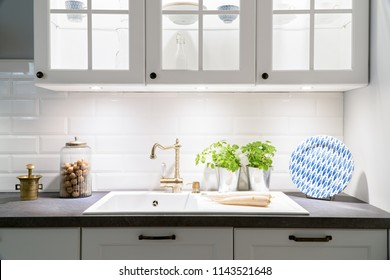 White and grey kitchen  - gold tap, plants, blue plate, vegetables, nuts, ceramic sink, compostition of kitchen artefacts, decoration