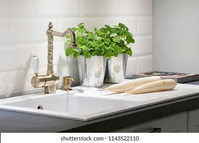 White and grey kitchen  - gold tap, plants, turnips, ceramic sink, compostition of kitchen artefacts, decoration