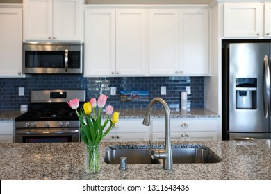 White and grey kitchen interior with spring flowers and granite countertop