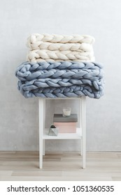 White and grey knitted woolen merino chunky blanket or plaid lying on white bedside table. Blanket of thick yarn. Light stylish cozy scandinavian room interior with grey stucco wall.