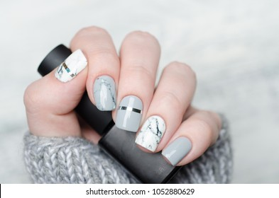 white grey marble manicure with silver stripe on grey background with nail polish bottle in hands