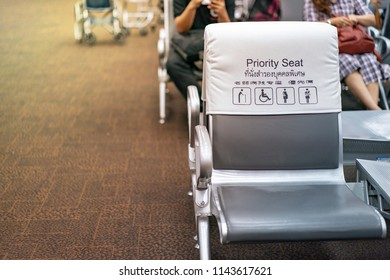 """White and grey piority seat near gateway in the airport, with blur passengers behind. (Thai and Chinese language  means """"piority seat"""")"""