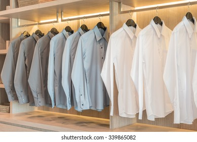 white and grey shirts hanging in wooden wardrobe