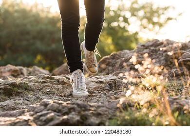 The white grunge shoes on the rock in park. Beautiful autumn background with bokeh and blurred background. Low depth of field. Detail of woman's legs.
