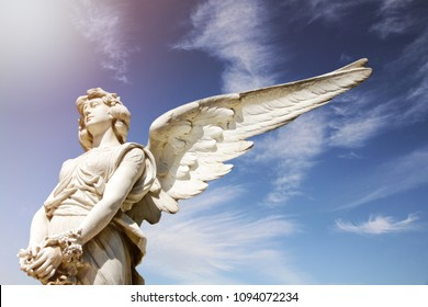 White guardian angel marble sculpture with open long wings across the frame and against a bright sunny blue sky with lens flare and glow. Sculpture hands holding a circle of flowers. Below perspective