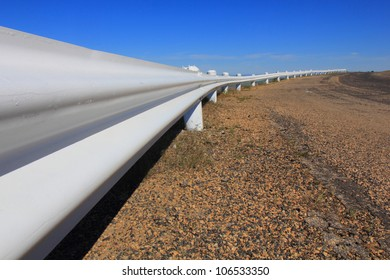 A white guardrail on a rural roadside with a nice perspective.