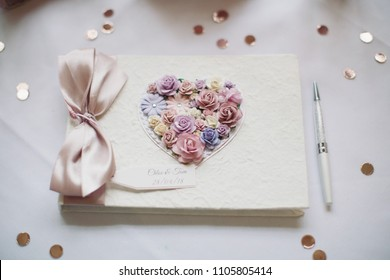 White guest book with flowers and a ribbon