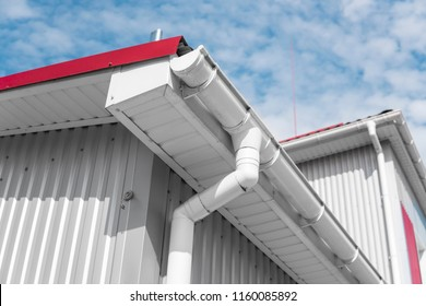 White guttering on a home with red roof against blue sky. Plastic guttering system. Guttering drainage pipe exterior.