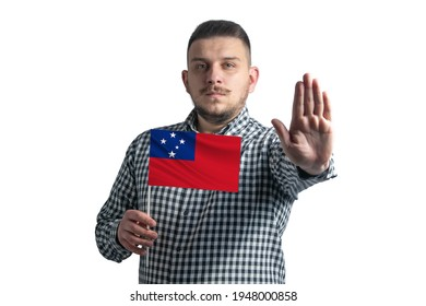 White guy holding a flag of Samoa and with a serious face shows a hand stop sign isolated on a white background.