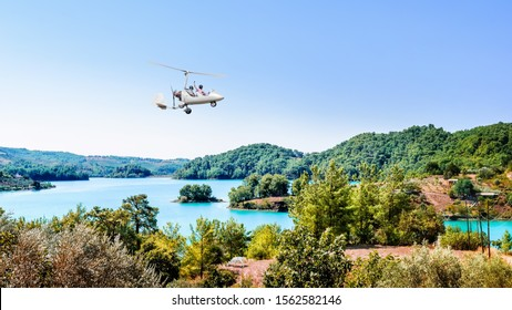 White gyroplane in blue sky over the Manavgats Lake, Turkey