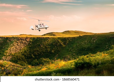 White gyroplane with two pilots at sunset in the sky over the hill. New technologies in aerial photography.