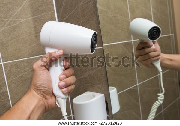 White Hair Dryer on wall in bathroom