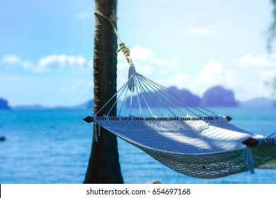 white hammock with clear blue sea and island in background