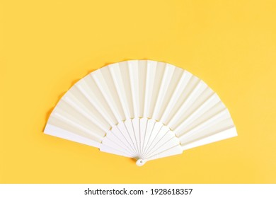 White hand fan on yellow background, top view