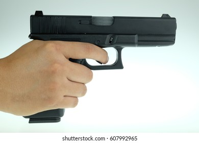 White hand holds gun isolated on white background.