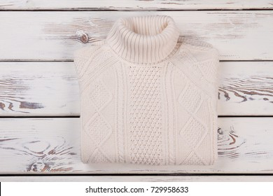 White hand knitted jumper with roll neck on rustic background. Warm handmade clothing for chilly weather.