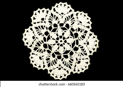 White hand made crocheted coaster lace doily on black background