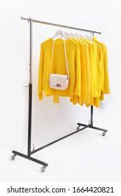 Weiße Handtasche mit einer Sammlung gelber, gelber Kleidung, Kleidung, Pullover, Hemd, Kleidung, Jacke, die auf Holzkleider hängt Kleiderbügel im Schrank oder Kleiderständer auf weißem Hintergrund