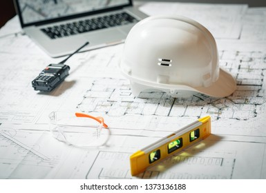 White hard hat, laptop  with drawings, glasses and walkie talkie with  and blueprints on a table. Architectural and construction concept