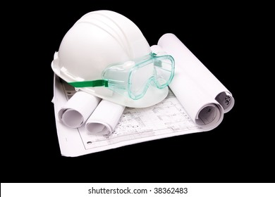 White hard hat with safety goggles on partially unrolled blueprints.  Isolated on black.