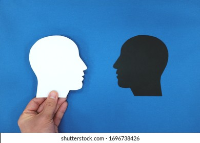 White head profile silhouette facing black shadow in blue background. Face fears, dark side, bipolar identity concept.