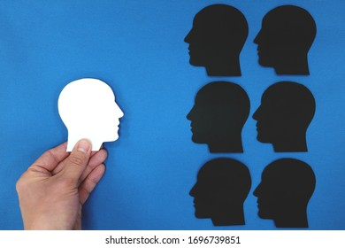White head profile silhouette facing black shadows in blue background. Face fears, dark side, mental health crisis concept.