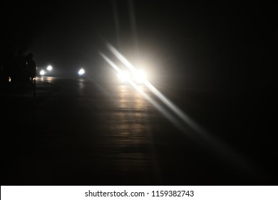 White headlamps of a running vehicle at night isolated unique blurry photo