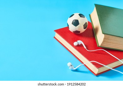 White headphone and old books, toy soccer, football ball on blue background. Audiobook concept. Online education. E-learning. Modern technology