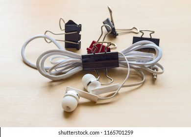 White headphones and binder clips on the table with birch texture