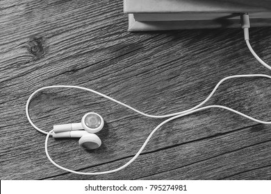 white headphones and a book. audiobook concept