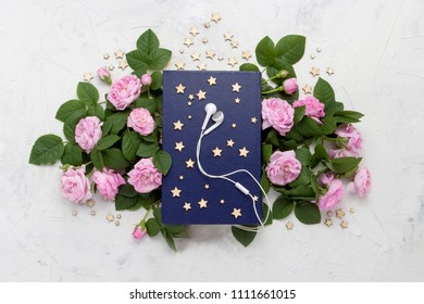 White headphones, Book with a blue cover, small stars and pink roses on a light stone background. Concept audiobooks. Flat lay, top view.