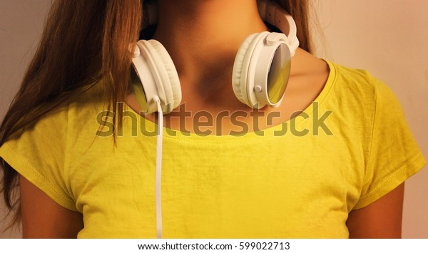 White headphones close-up hanging on the neck of the young girl in a yellow T-shirt.
