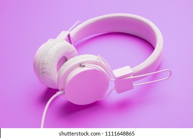 White headphones with cord on an empty purple background.