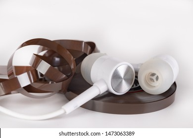 White headphones and magnetic tape with call recordings. Eavesdropping accessories. Light background.