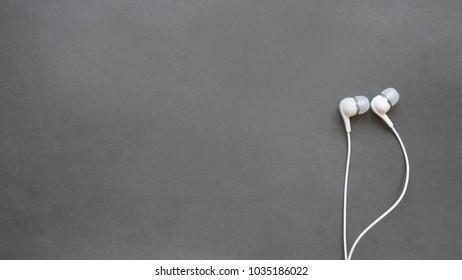 white headphones on black background, copy space