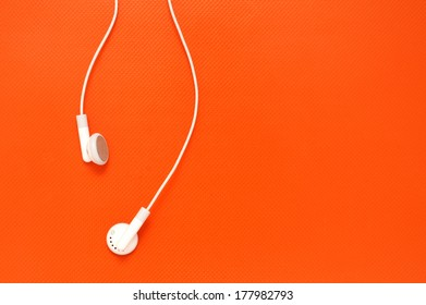 White headphones on orange plastic background with copy space