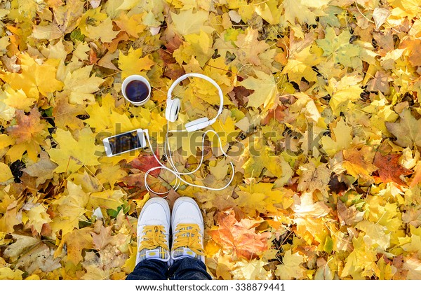 White headphones with a player and a cup of tea and coffee on a background of yellow leaves. Autumn mood. Music autumn.