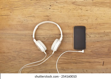 White headphones and smart phone on wood