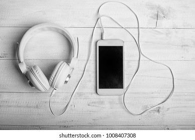 White headphones and smatphone on white board