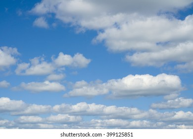 White heap clouds in the blue sky. Cloudscape over horizon. Heaven.