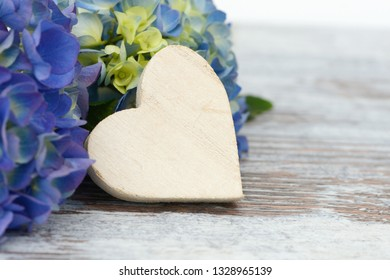 White heart and flowers lying on wood