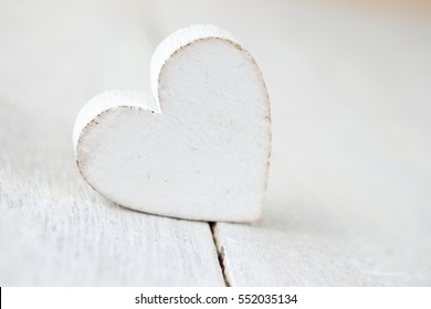 White heart on white wooden background, copy space