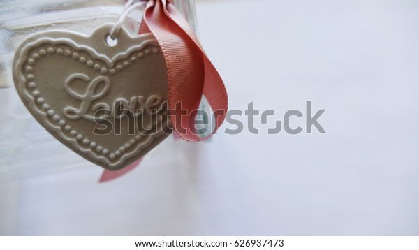 White heart  with pink ribbon, jar and love