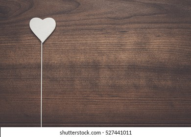 white heart shape on stick over wooden background
