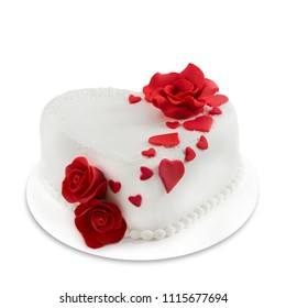 White heart shaped marzipan cake with red roses and red marzipan hearts and white sugar pearls on white plate isolated on white background