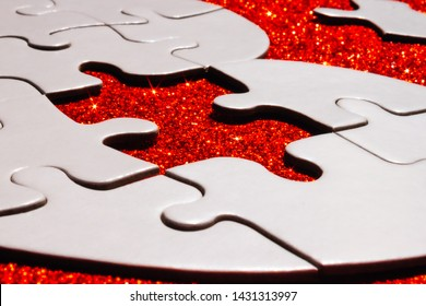 White heart shaped puzzle with missing part on red sparkle background.