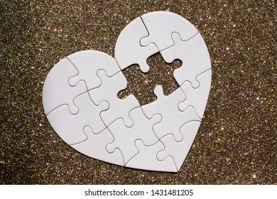 White heart shaped puzzle with missing part on golden sparkle background.