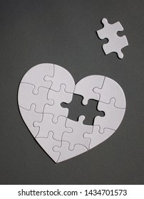 White heart shaped puzzle with missing part on dark gray background.
